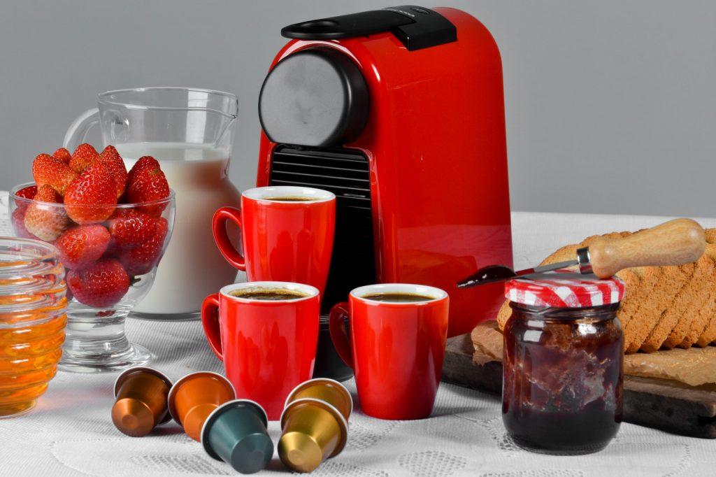 Na foto uma cafeteira com xícaras e comidas ao redor.