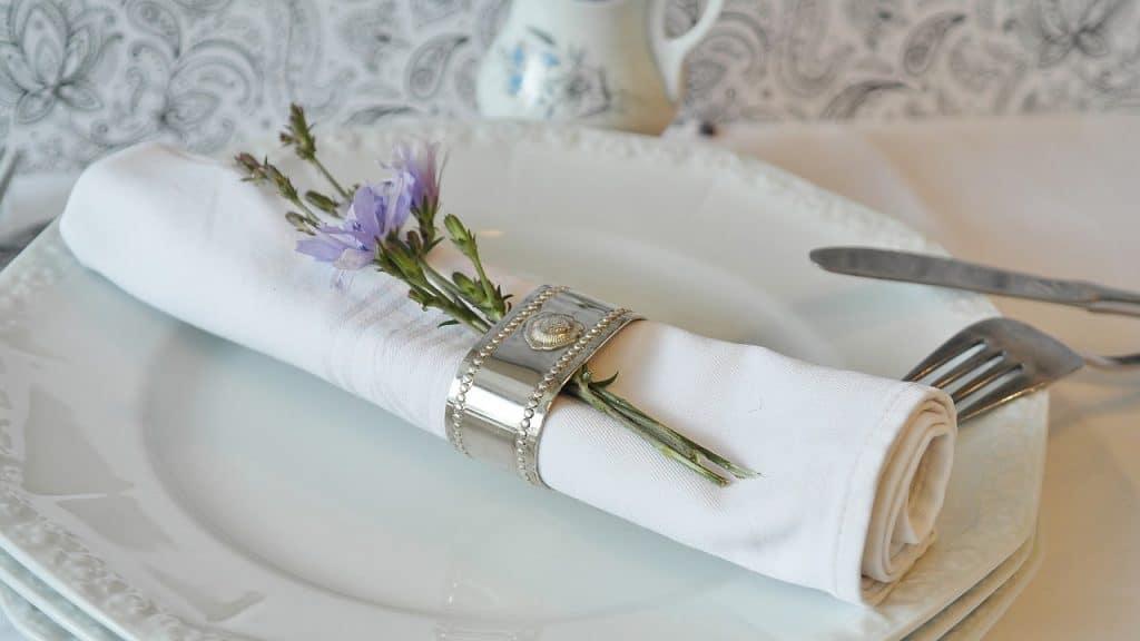 Imagem de guardanapo preso com porta guardanapo de metal em cima de prato.