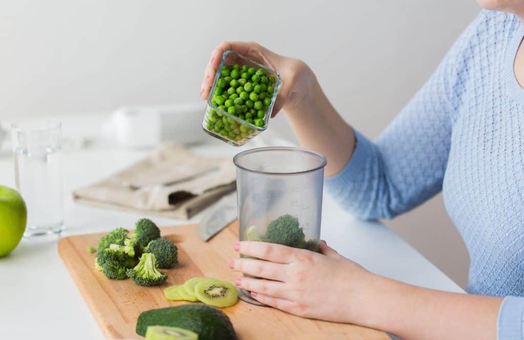Na imagem uma mulher despeja ervilhas no copo medidor.