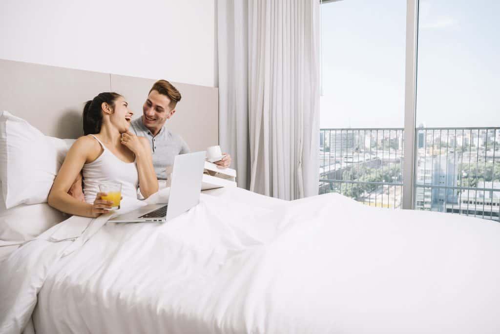 Casal tomando café da manhã em sua cama com jogo king size.