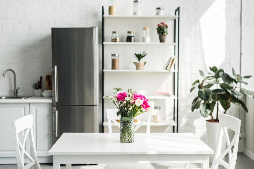 Geladeira inox em cozinha branca.