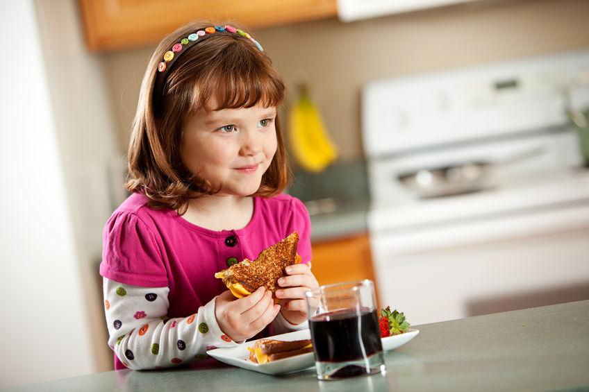 Menina comendo misto quente