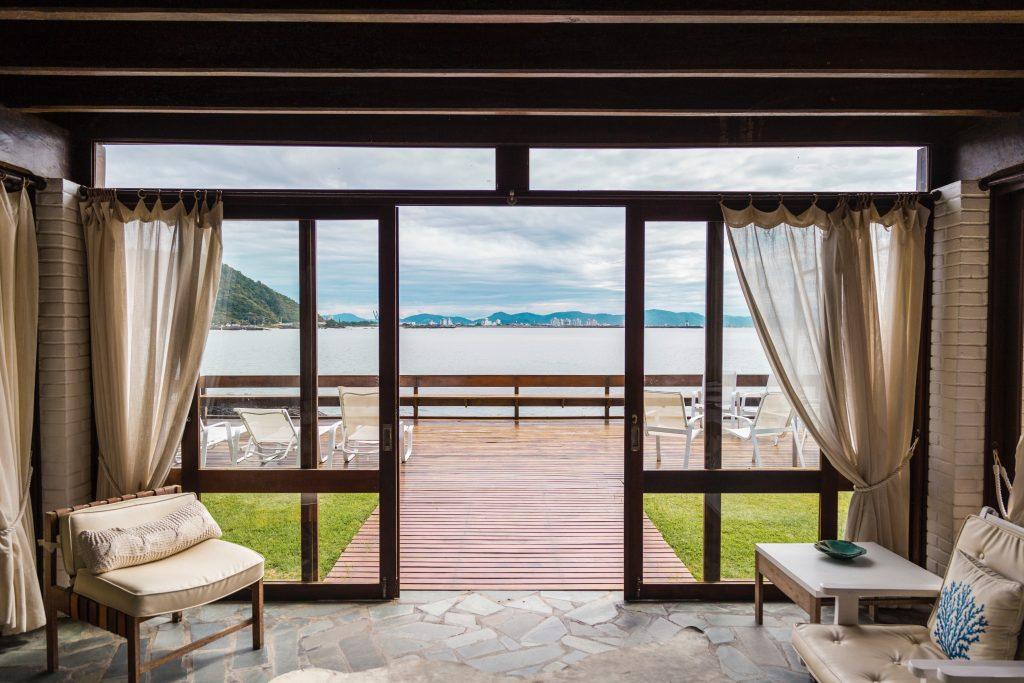 Foto de uma varanda com deck que dá pro mar. Na parte interna, uma sala com porta de vidro e cortina bege, combinando com a decoração do ambiente.