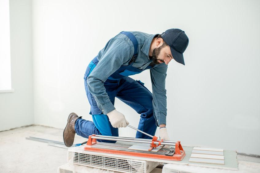 Imagem mostra um homem usando um cortador de piso.