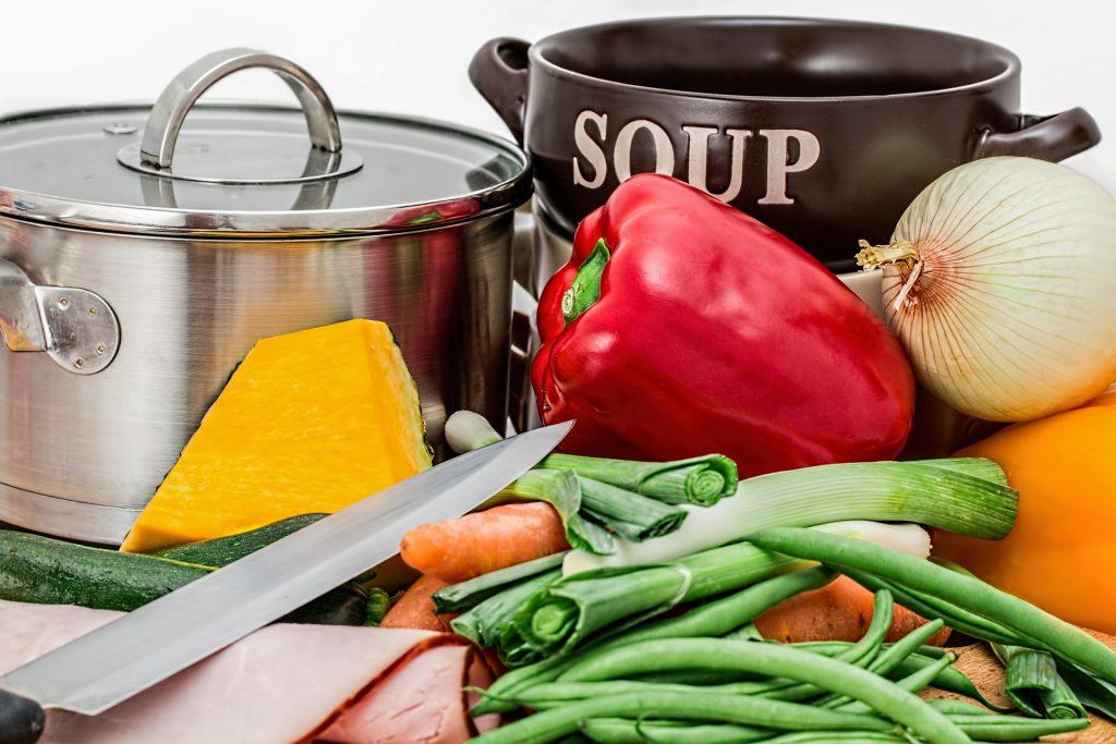 Ingredientes para sopa ao lado de caldeirão pequeno em inox