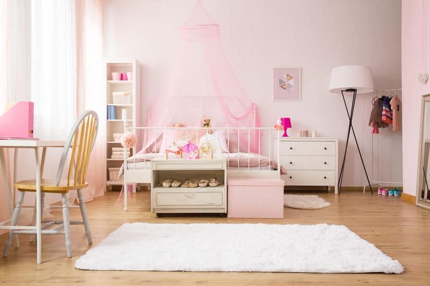 Imagem de quarto infantil de menina com cômoda branca ao lado da cama.