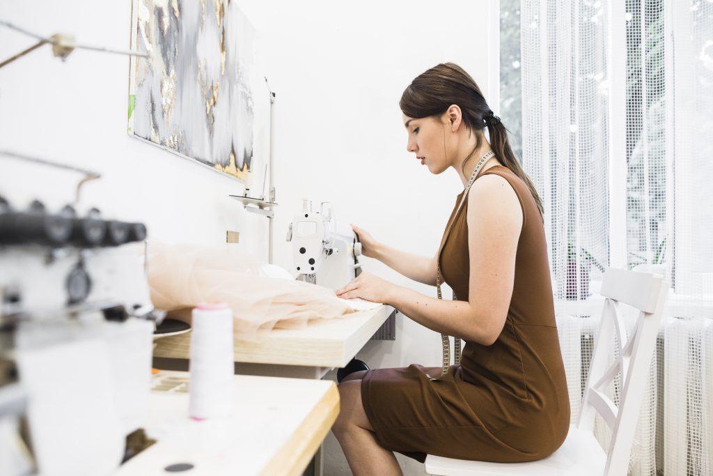 Imagem lateral de moça sentada à mesa trabalhando em máquina de costura