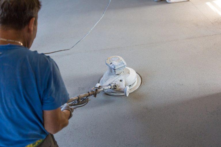 Imagem mostra um homem usando uma enceradeira industrial em um piso liso.