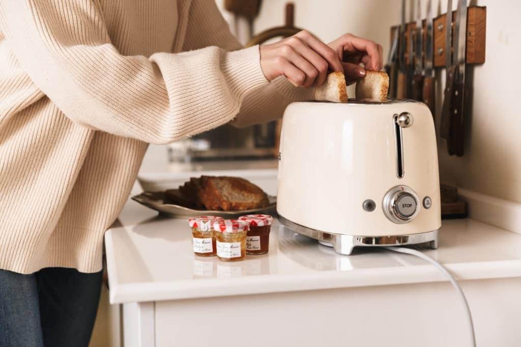 Imagem de uma mulher colocando pães em uma torradeira, próximo à uma barra magnética com facas.