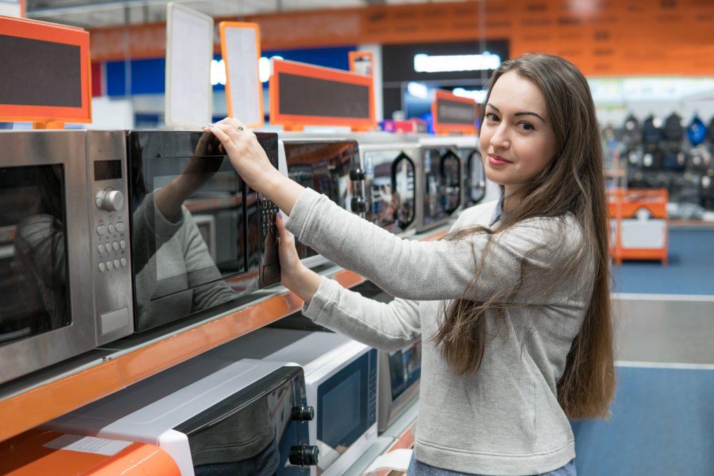 Imagem de uma mulher analisando um forno micro-ondas.