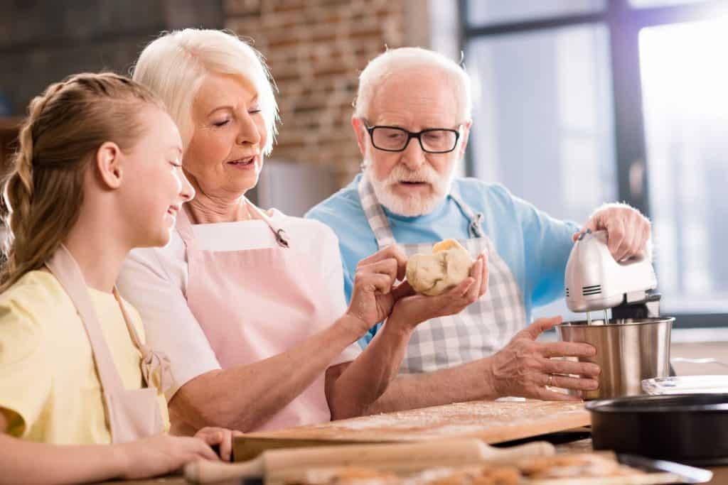 Foto de um casal de idosos e uma menina fazendo uma receita com a ajuda de uma batedeira.