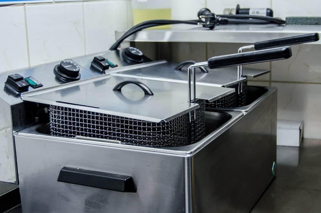 Imagem de escumadeira metálica apoiada em fritadeira profissional de aço inoxidável.
