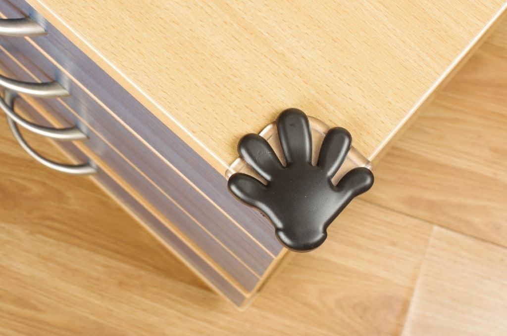 Um protetor de quina em formato de mão fixado num móvel.