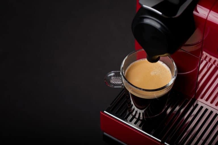 Na foto uma cafeteira vermelha com um xícara de café cheia.