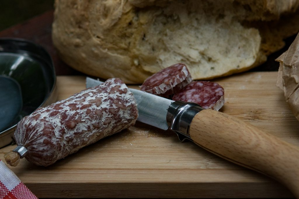 Imagem mostra uma pequena faca ao lado de um salame fatiado em um acampamento.
