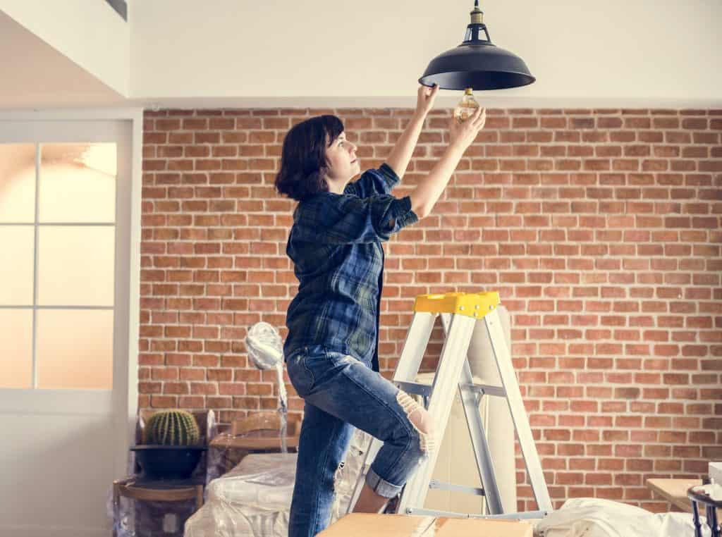 Na foto uma mulher trocando uma lâmpada.