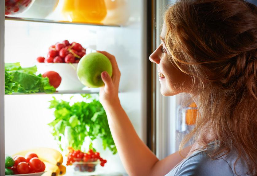 Mhulher segura porta da geladeira enquanto olha para seu interior