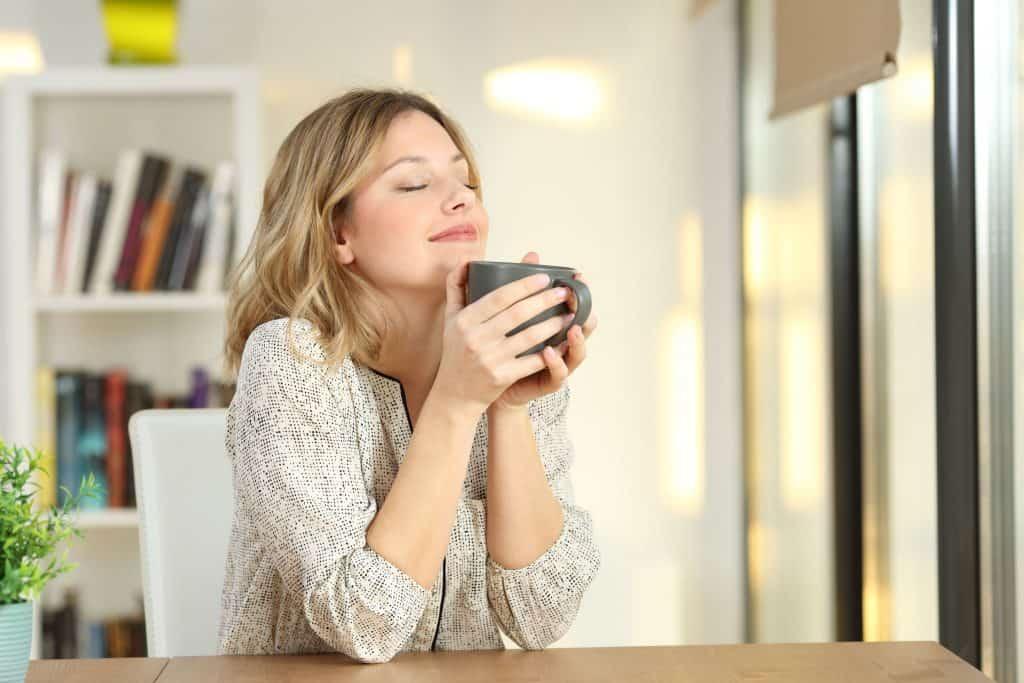Mulher sentada em uma bancada segurando uma caneca com cara de contentamento.