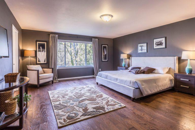 Na foto um qualquer de casal com piso de madeira, janela e móveis.