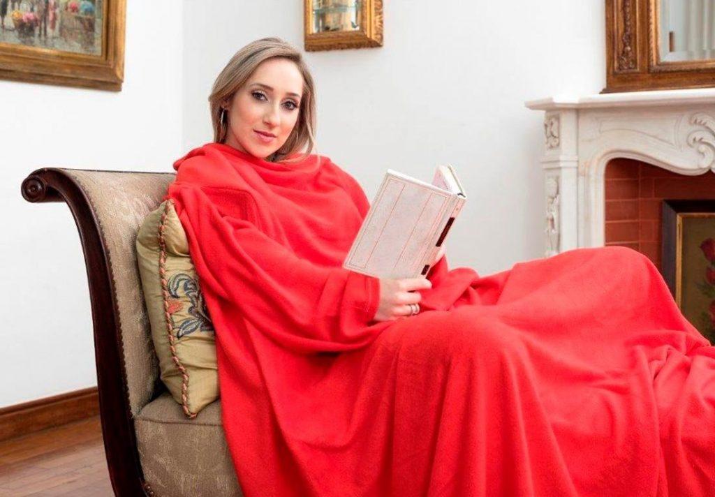Na foto uma mulher usando coberta e lendo um livro.