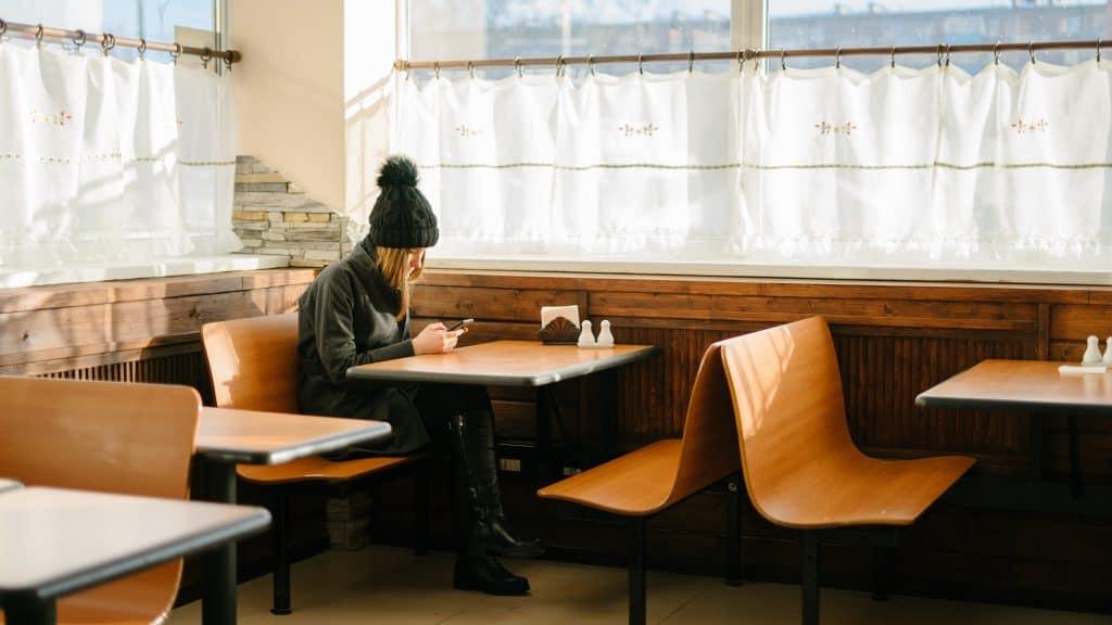 Imagem de mulher sentada em mesa de restaurante com porta guardanapo sobre ela.