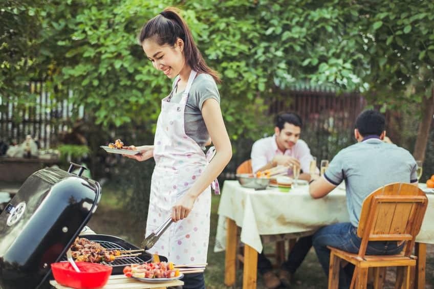 Imagem de um casal preparando um churrasco em um acampamento de trailers.