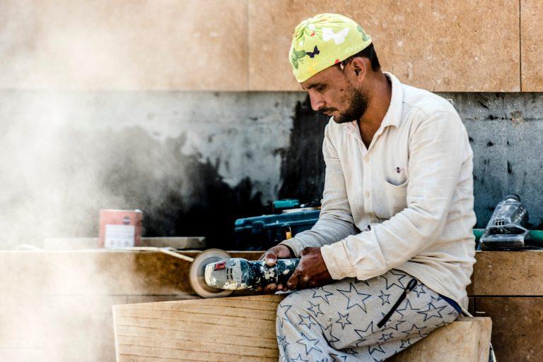 Imagem mostra um homem trabalhando com uma esmerilhadeira a bateria.