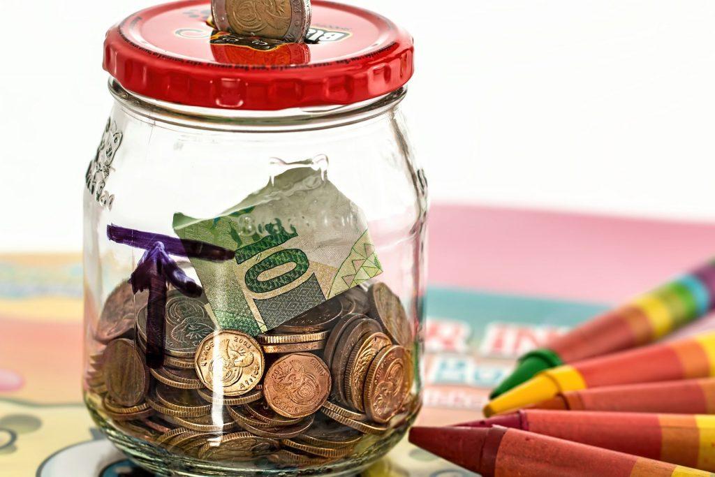 Um cofrinho feito a partir de um pote de vidro com tampa metálica possui notas e moedas de dinheiro no seu interior, enquanto ao seu lado estão cinco giz de cera.