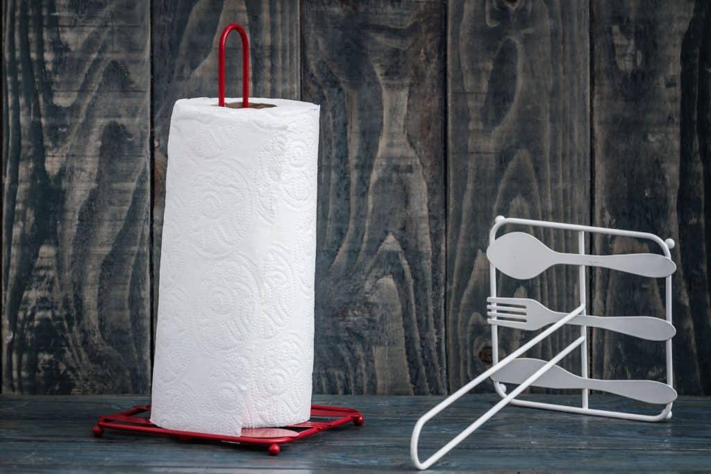 Dois modelos de porta papel toalha, um deitado vazio e outro em pé com um rolo de papel toalha, em cima de uma superfície de madeira.