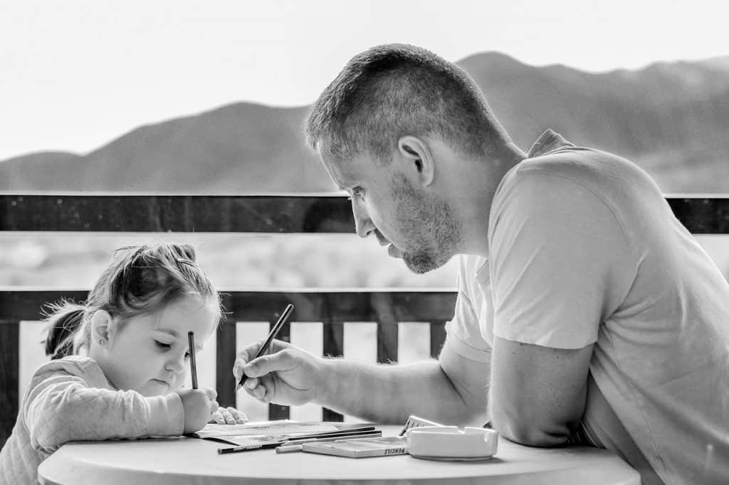 Imagem mostra um homem e uma menina desenhando juntos.