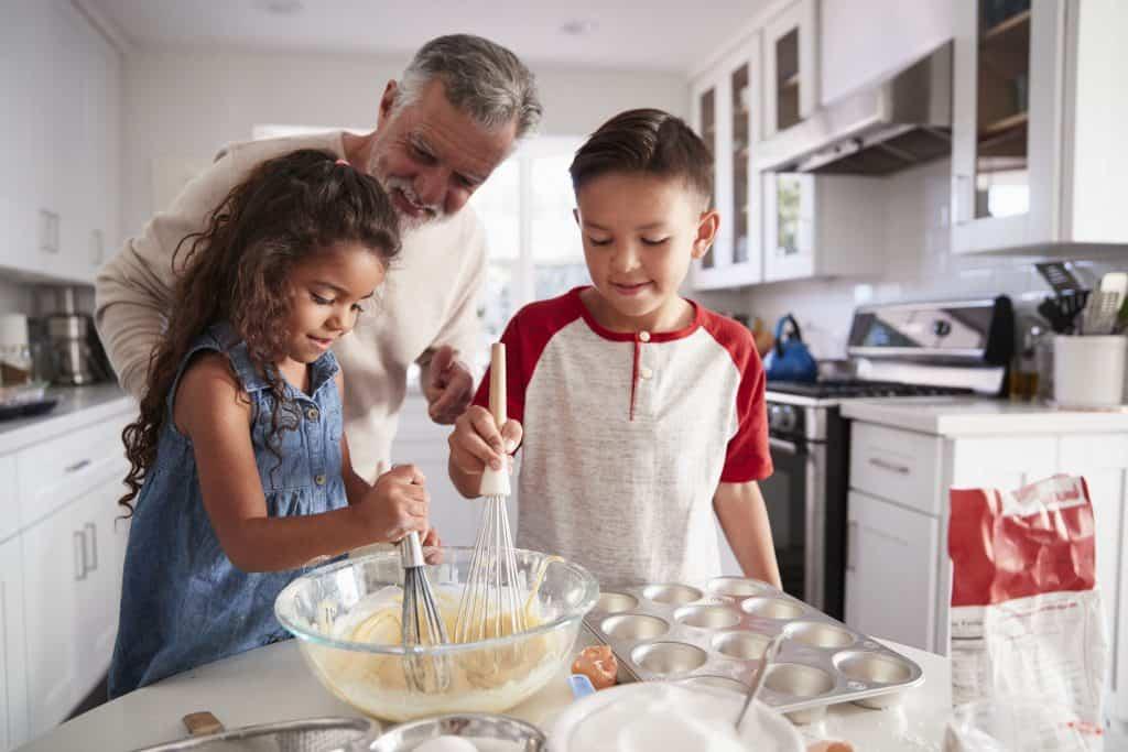 Na foto um senhor com uma menina e um menino dentro de uma cozinha preparando cupcakes.