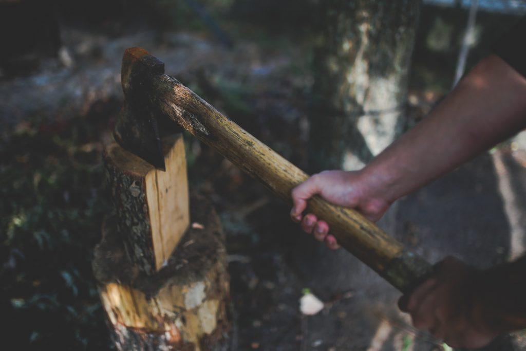Mãos e braços masculinos segurando um machado apoiado em um pedaço de tronco de árvore