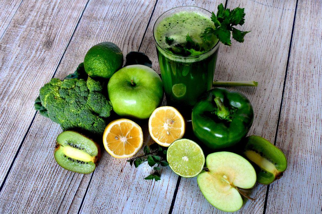 Na foto um copo de suco verde com diversas frutas ao seu redor.