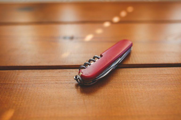 Imagem mostra um canivete vermelho sobre uma mesa.