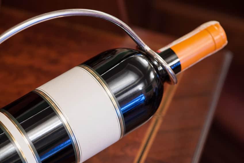 Imagem de garrafa de vinho em suporte de metal.