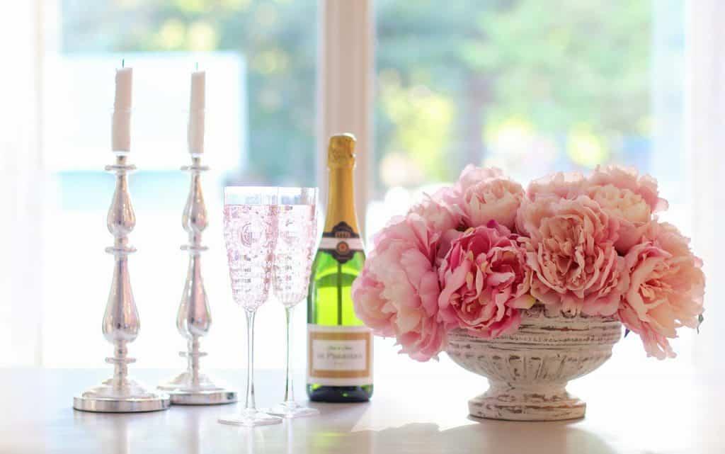 Foto de duas taças de champagne sobre uma mesa ao lado de um espumante, velas e vaso de flores.