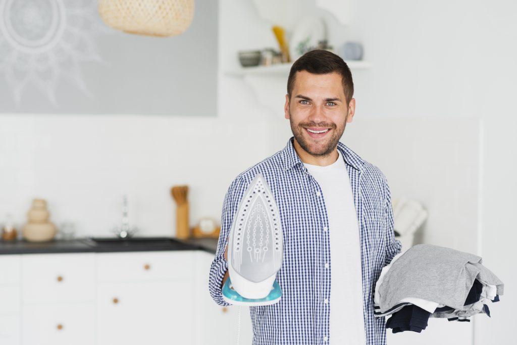 Rapaz sorri enquanto segura ferro de passar em uma mão e pilha de roupas em outra