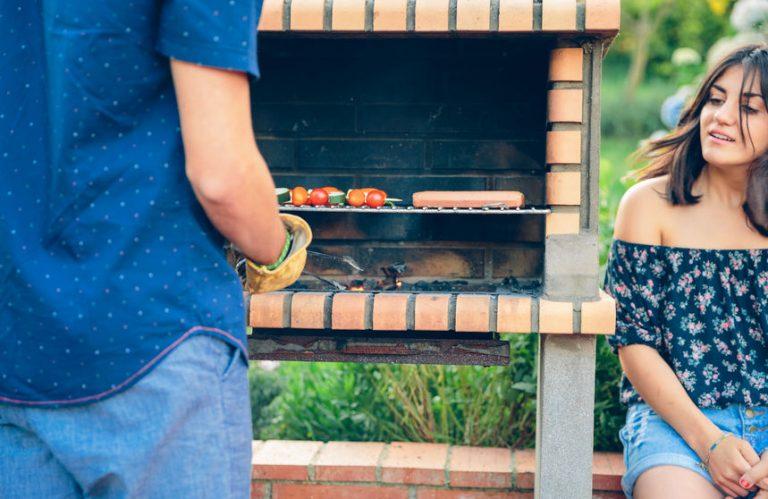 Imagem de uma garota sentada ao lado de uma churrasqueira de tijolinho enquanto homem prepara o churrasco.