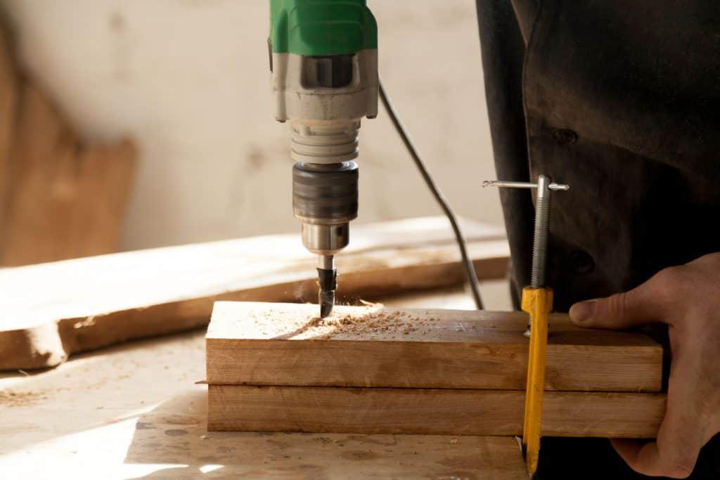 Imagem mostra uma mão usando furadeira em madeira.
