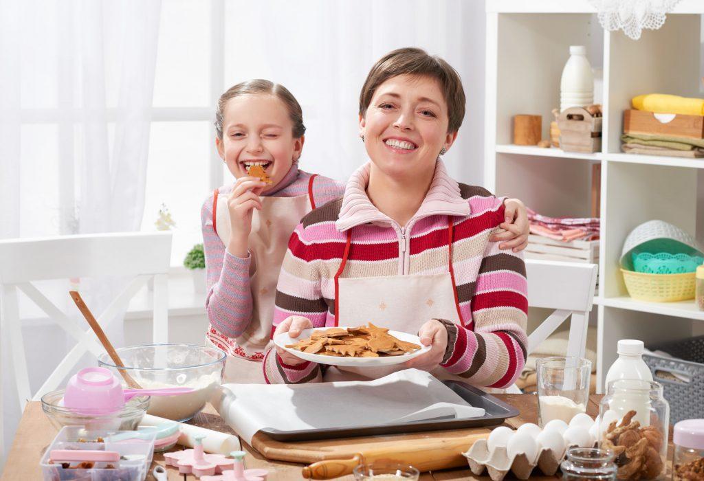 Imagem de uma mulher e filha fazendo bolachas na cozinha.
