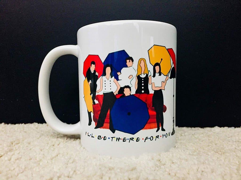 Uma caneca branca, com uma ilustração que contém os seis personagens da série Friends, encontra-se em cima de um tapete claro em um fundo escuro/preto.