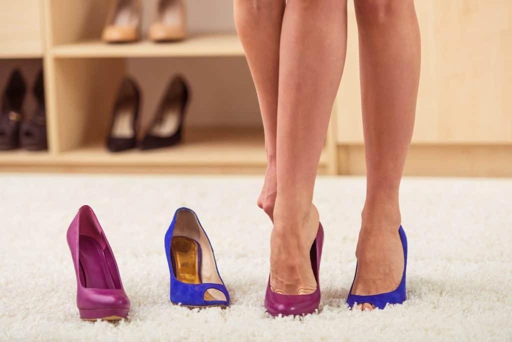 Pernas de mulher provando sapato de salto alto.