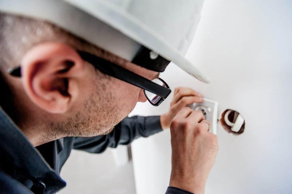 Um eletricista realiza uma instalação em uma tomada.
