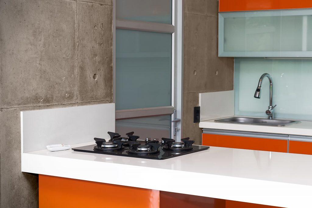 Linda cozinha moderna e organizada com cooktop 4 bocas sobre bancada branca.