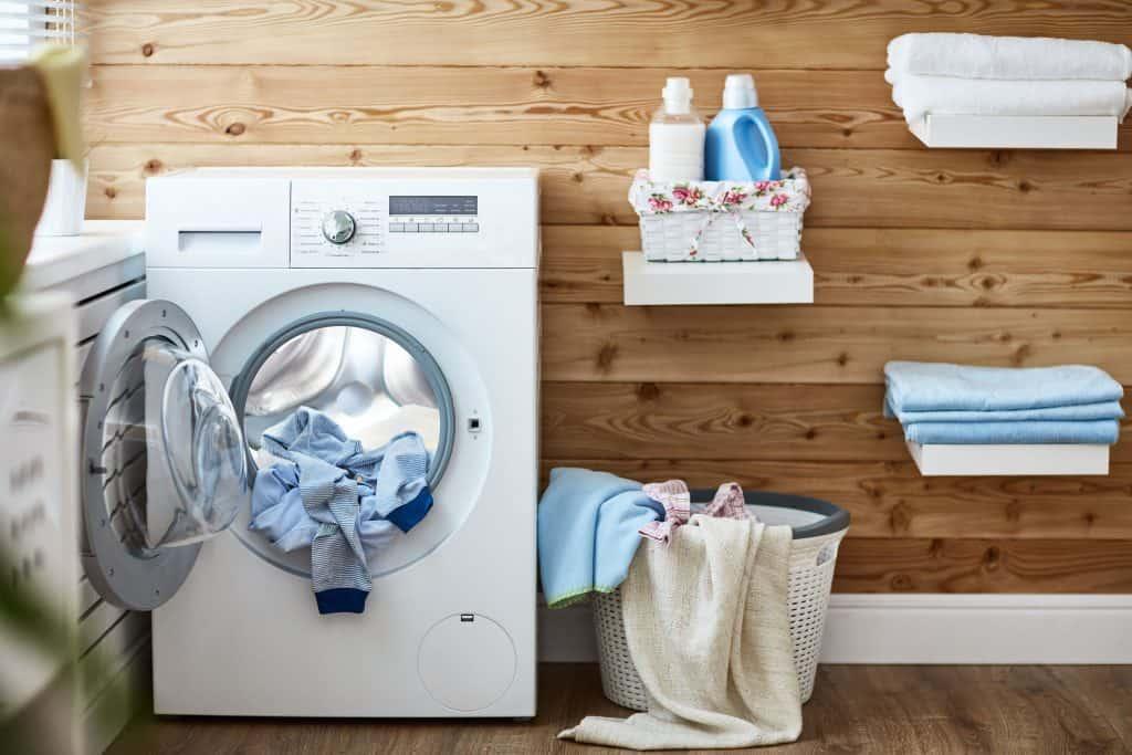 Imagem de máquina de lavar roupas com roupa dentro em lavanderia.