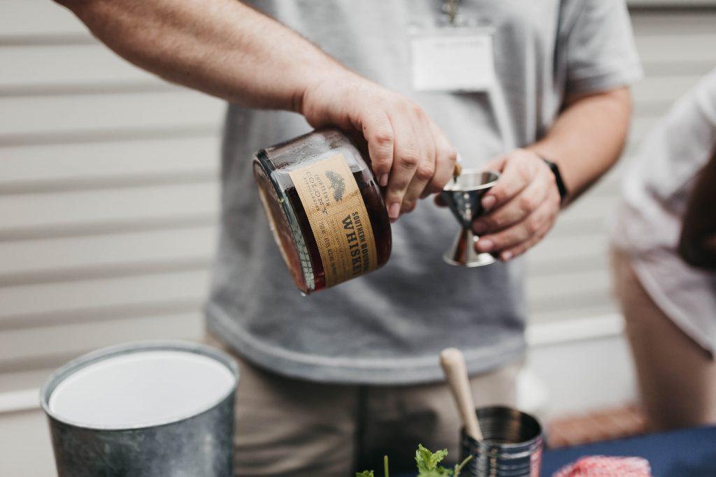 Um homem está segurando uma garrafa de uísque com a mão direita e um dosador com a mão esquerda. Ele despeja a bebida alcoólica dentro do dosador.