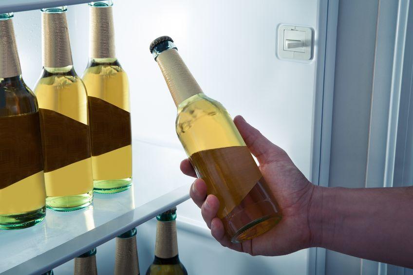Homem pegando cerveja no frigobar.