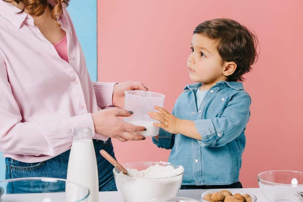 Na imagem uma mãe e filho preparam receita juntos, eles seguram um copo medidor, há tigelas e ingredientes sobre a mesa.