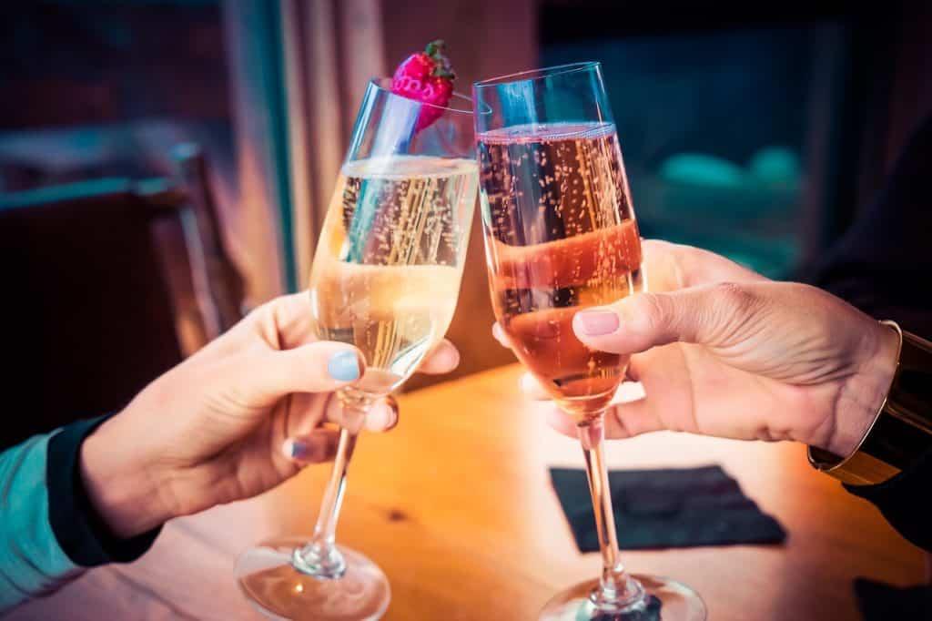 Foto de duas pessoas brindando com taça de champagne.