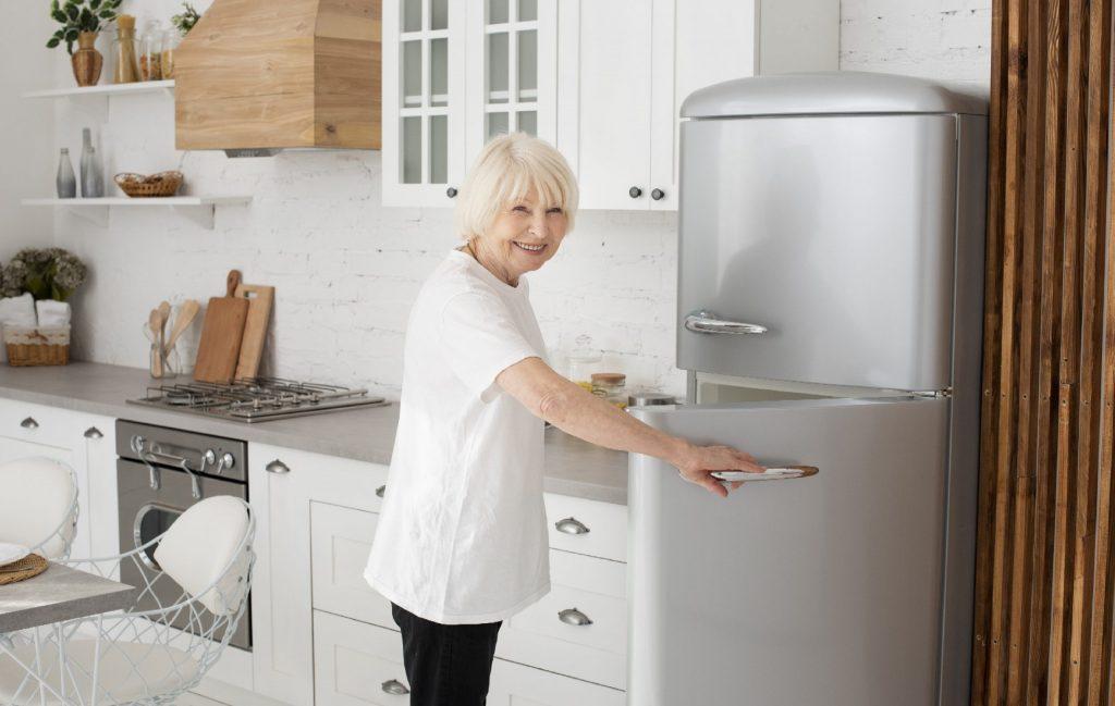 Senhora sorri para foto enquanto abre geladeira
